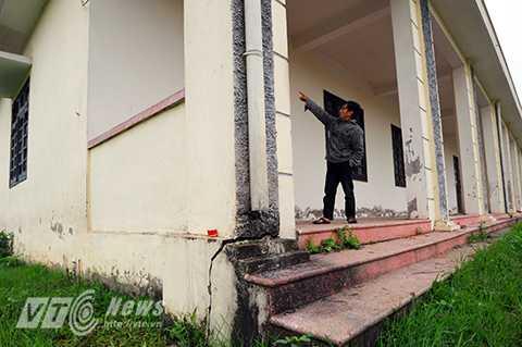 Ông T, một người dân sống cạnh khu vực trường học đang chỉ cho phóng viên những mảng tường, bậc tam cấp của tòa nhà bị nứt vỡ, mặc dù ngôi trường chưa hề được đưa vào sử dụng
