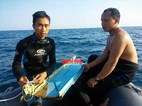 Hai chiến sĩ vừa đưa mảnh vỡ máy bay SU 22 lên từ lòng biển - Ảnh: HOÀNG VĂN SỐ