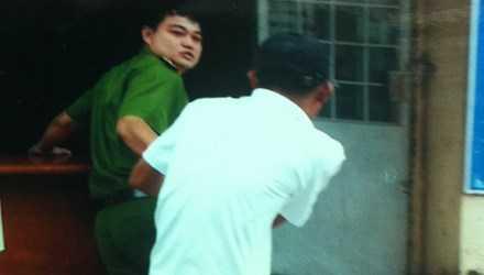 Ông Phúc còng tay và đang lôi anh Sang qua phòng làm việc đóng kín tại trụ sở Công an P.Trường Thạnh, Q.9, TPHCM. Ảnh do gia đình cung cấp