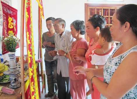 Người thân anh Huỳnh Xuân Điền đau đớn bên bàn thờ khi anh bị nạn, được chôn cất mà người thân không hề hay biết. Ảnh: TẤN LỘC