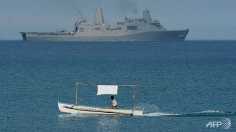 Một thuyền đánh cá của dân Philippines chạy gần tàu hải quân của Mỹ USS Green Bay (LPD-20) trong cuộc diễn tập chung ở khu vực cách bãi Scarborough 220 km về phía Đông -  Ảnh: AFP