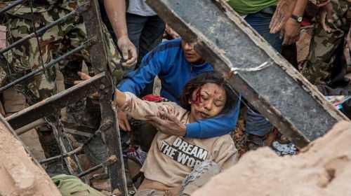 Một phụ nữ sống sót được cứu sống từ đống đổ nát ở thị trấn Dharara. Ảnh: Reuters