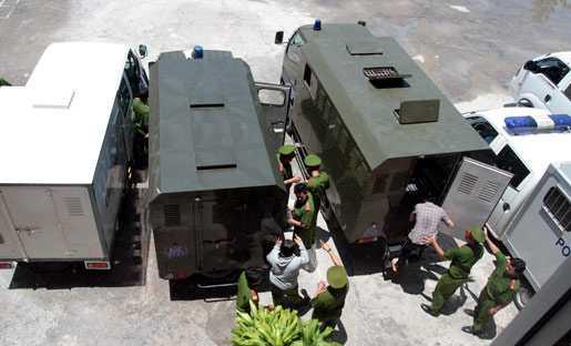 Lực lượng bảo vệ đưa các bị cáo ra xe bịt bùng về trại tạm giam.