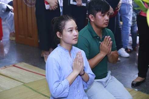 Vợ anh thẫn thờ trước bàn thờ của chồng.
