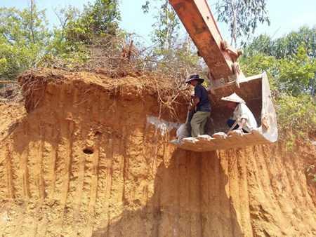 Người dân thuê xe cẩu thu gom những mảnh xương lộ thiên vì mộ bị đào xới.