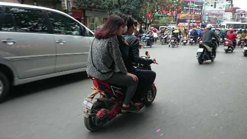 Xe máy điện gắn 'biển số đồ chơi' vô tư đi trên phố Đại La, Hà Nội.