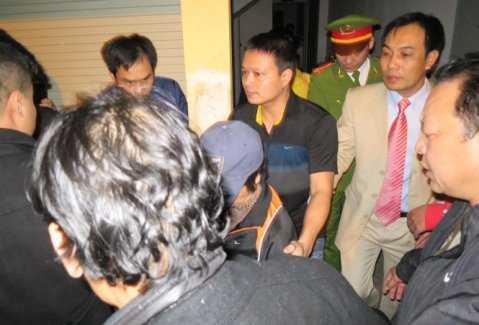 Bà Châu Thị Thu Nga (giữa, chụp mũ) bị bắt giữ và dẫn giải về trại giam vào tối khuya 7-1 - Ảnh: LÊ KIÊN