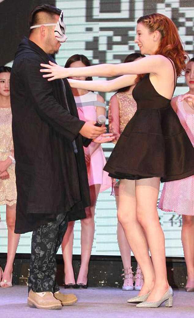 Rola Misaki ôm lấy một người đàn ông đang đeo              một chiếc mặt nạ, được cho là vị tỷ phú đã thuê cô tại một sự kiện gần              đây ở Bắc Kinh