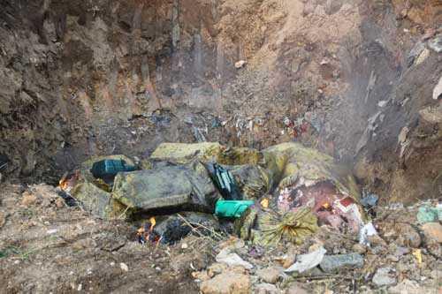 Các bao chứa thùng xốp đựng nầm lợn được đốt và bỏ xuống hố chôn trước sự chứng kiến của cơ quan chức năng (Ảnh: báo Bắc Giang)