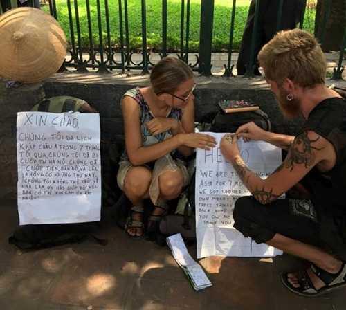 Hai du khách bị mất tài sản, viết thông báo trước cổng Văn Miếu Quốc Tử Giám (Ảnh: internet)