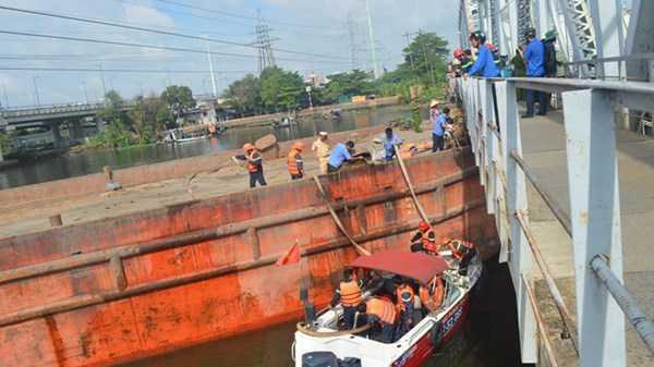 Lực lượng cứu nạn – cứu hộ thuộc cảnh sát PCCC TPHCM bơm nước để nhấn chìm sà lan