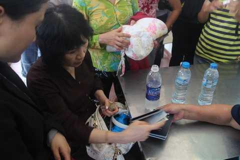 Bà Huỳnh Thị Cẩn cầm trên tay 3 hộ chiếu của người thân, rưng rưng xúc động...