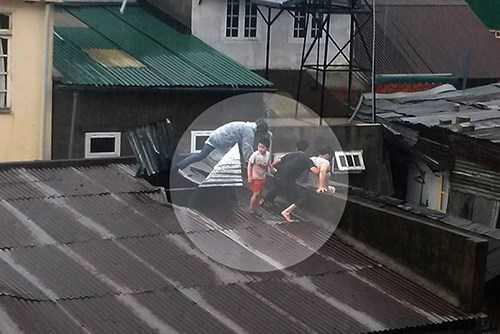 Người dân cùng lực lượng chức năng phải dỡ mái nhà cứu người mắc kẹt trong mưa lũ. (Ảnh: Thanh Niên)