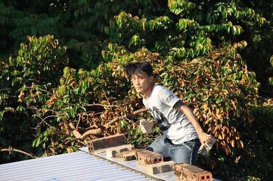 Thanh niên cầm gạch đá, cố thủ trên nóc nhà dân