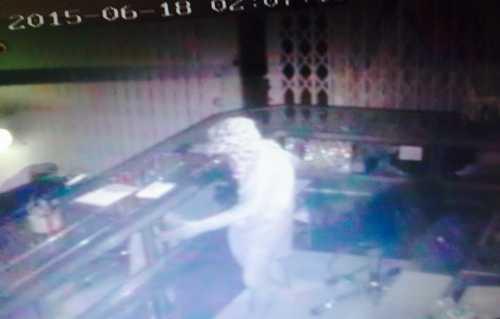 Hình ảnh camera ghi lại vẻ bình thản của tên trộm khi lấy vàng. Ảnh: Cửu Long