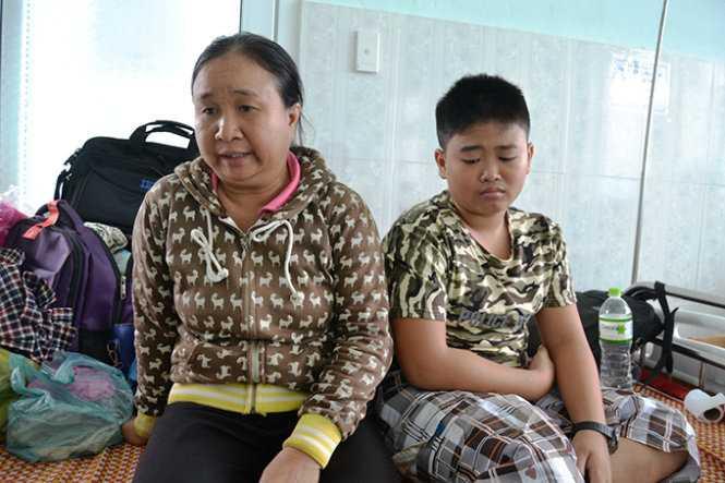Hai mẹ con bà Đỗ Thị Huệ (vợ nạn nhân Vũ Văn Nam) ở Trung tâm Y tế Phước Sơn - Ảnh: Lê Trung