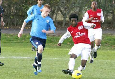 Cầu thủ nhí của Arsenal (phải) vẫn thi đấu với giày tất