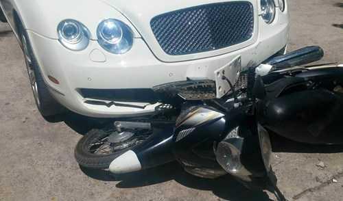 Chiếc xe máy bị mắc kẹt trong gầm ô tô. Ảnh: Otofun.