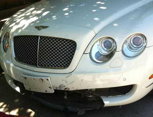 Phần đầu xe Bentley bị hư hỏng nặng, biển số tung ra ngoài. Ảnh: CTV.
