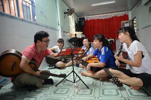 Thầy Kim Seungki (Hàn Quốc - trú ở chung cư gần nhà) thường xuyên đến dạy đàn cho các em. Ảnh: DUYÊN PHAN