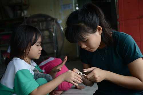 Chị lớn Ngọc Châu (phải) cắt móng tay cho các em. Ảnh: DUYÊN PHAN