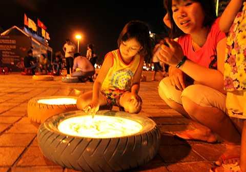 Vẽ tranh cát trên lốp xe tái chế là một trong những hoạt động độc đáo của