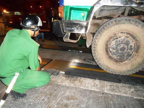 Lực lượng TNXP điều khiển cân di động cho khớp bánh xe tránh gây hư hỏng cân điện tử. Ảnh: Tử Long