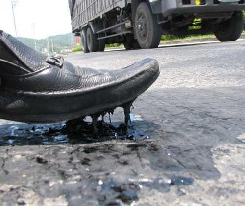 Nhựa đường dính chặt vào đế giày. Ảnh: Minh Cương.
