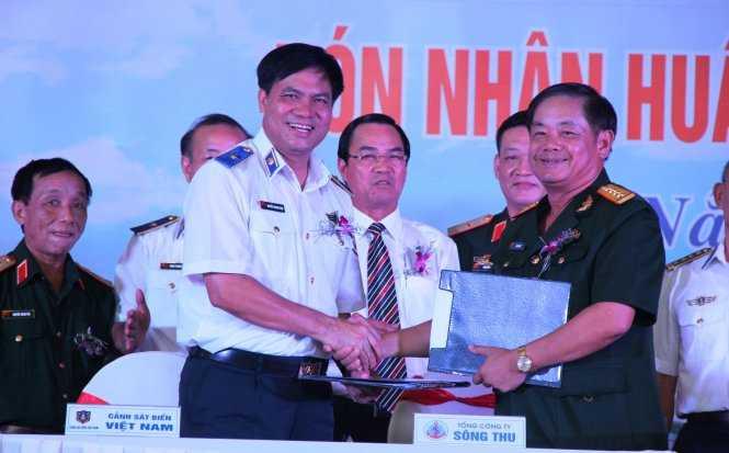 Đại tá Hà Sơn Hải (phải) - Tổng giám đốc tổng công ty Sông Thu bàn giao biên bản giao hai tàu cho đại diện cảnh sát bển Việt Nam - Ảnh: Phan Thành