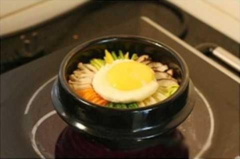 Cuối cùng cho trứng chiên lên trên mặt, sau đó hâm nóng lại cho tới khi bạn nghe thấy tiếng xèo xèo thì có thể tắt bếp là dùng được.