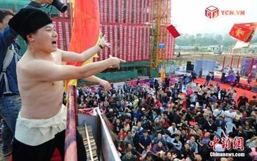 Đại gia cởi trần đứng từ giàn giáo cao 100m rải phong bao lì xì cho đám đông