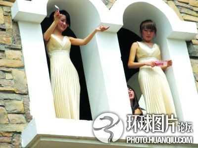 Những cô gái trong bộ váy màu trắng đứng từ cửa sổ khách sạn rải tiền xuống dưới cho khách nhặt