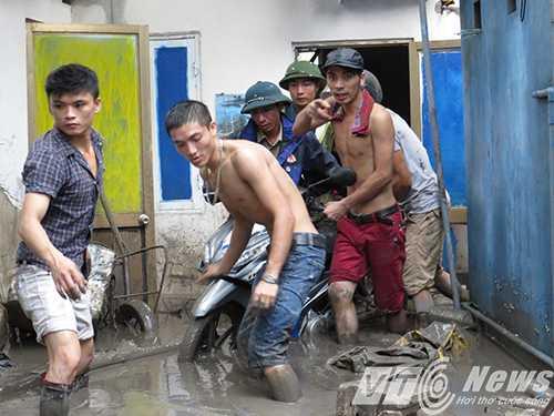 Thanh niên giúp nhau vận chuyển chiếc xe máy ra khỏi nhà - Ảnh MK