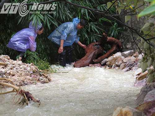 Người dân đang cố gắng bê đá kè bờ chân tường chống sạt lở bởi mưa lũ - Ảnh MK