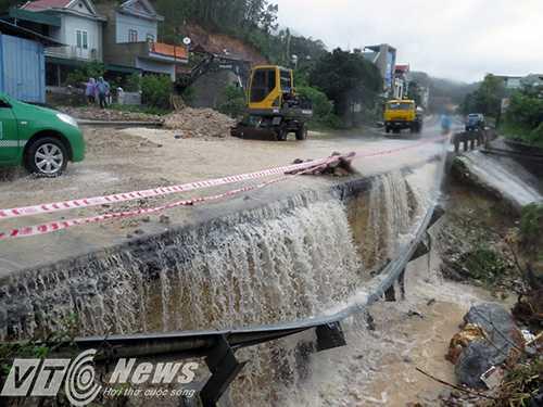 Lượng nước đang chảy tràn qua đường tránh Cửa Ông, khoét sâu vào tim đường, có nguy cơ sạt lở nghiêm trọng - Ảnh MK