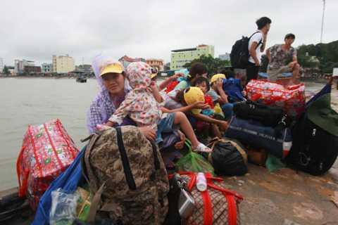 Du khách đồ đạc lỉnh kỉnh ngồi chờ ở cầu cảng- ảnh Tiến Thắng