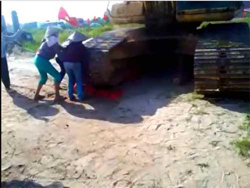 Người dân cố lao vào nâng bánh xe xúc để cứu bà Châm nhưng bất thành - Ảnh cắt từ clip