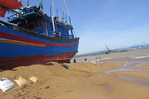 Tàu cá PY-96188 bị triều cường vùi trong cát.