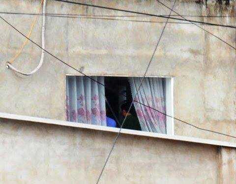 Hình cơ quan chức năng  đang thực nghiệm lại hiện trường trên lầu phía sau căn nhà ông Lê Văn Mỹ
