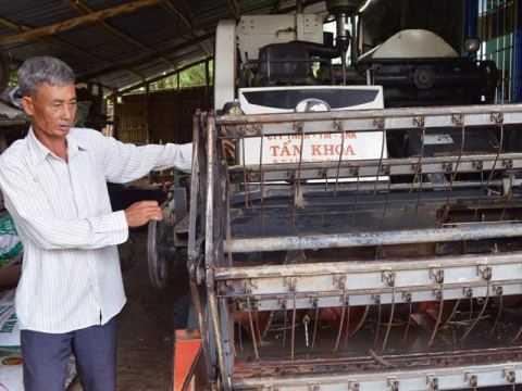 Ông Buôl kiểm tra chiếc máy gặt đập liên hợp mới mua. Ảnh: Chúc Ly