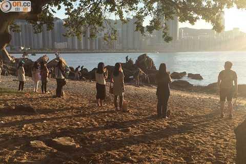 Phụ nữ Hồng Kông đứng trên bãi biển và nhìn thẳng vào mặt trờilúc hoàng hôn