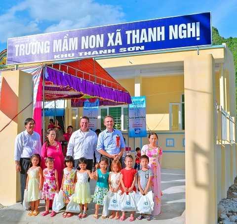 Các khách mời chụp hình lưu niệm với các bé trước ngôi trường mới