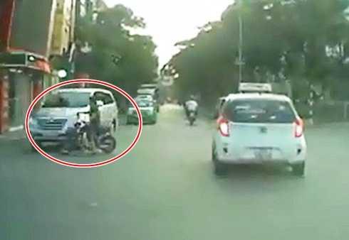 Người phụ nữ đi xe đạp điện vượt đèn đỏ, đâm vào ô tô (Ảnh cắt từ clip)