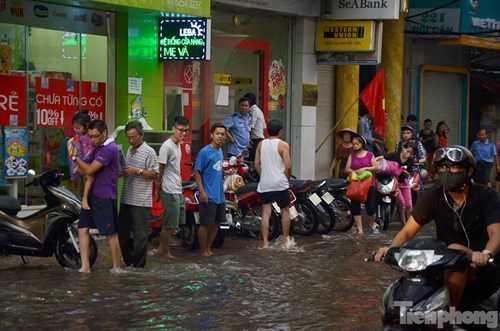 Nhiều người dân đi lên vỉa hè do nước ngập.