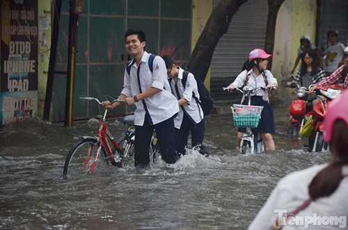 Các em học sinh vất vả dắt xe qua chỗ nước sâu.