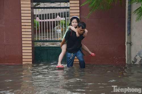 Một em nhỏ được người lớn cõng qua chỗ nước ngập.