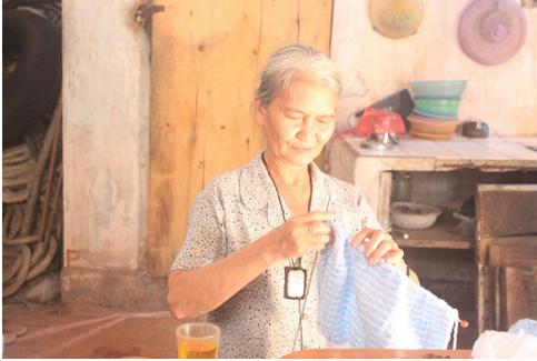 Bà Mang Thị Bộ cần mẫn đang áo len tại nhà.