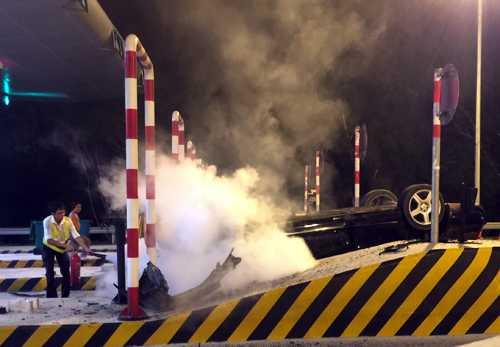 Lực lượng nhân viên trạm thu phí nhanh chóng dùng bình chữa cháy xịt vào chiếc xe Mercedes bị hất tung, đang bốc khói nghi ngút. Ảnh: CTV