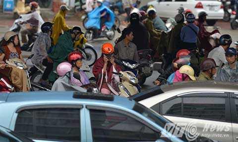 Người dân đi xe máy phải dừng xe dưới chân đường cao tốc trên cao để trú mưa và chờ hết tắc đường.