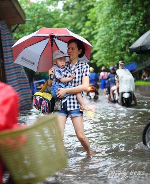 Tay che ô, lội nước bế con đến trường học ở Hà Nội